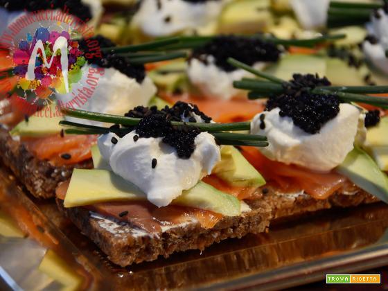 Crostoni di segale con salmone, panna acida, avocado e caviale