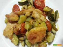 Nuggets di pollo al forno su letto di pomodorini e zucchine