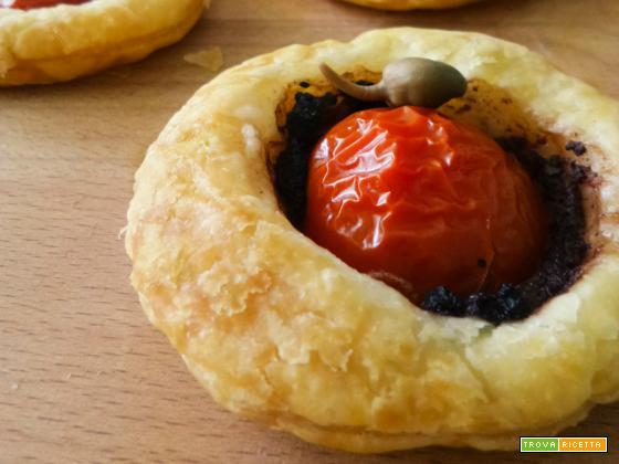 Pizzette di sfoglia con capperi, paté di olive nere e pomodorini