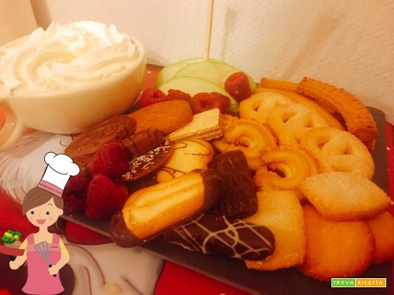 Cioccolata calda con panna, servita con biscotti danesi al burro e frutta
